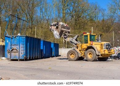 Ronneby, Sweden - March 27, 2017: Documentary of public waste station. Volvo L90E wheel loader emptying trash in blue container.