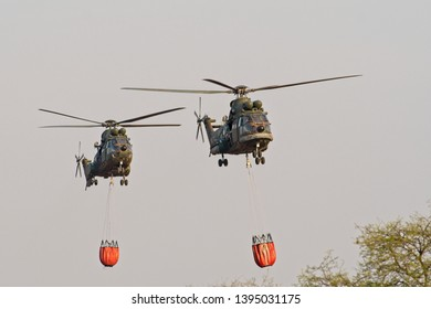 ROODEWAL, SOUTH AFRICA-SEP 17 2018: Two Oryx helicopters with Bambi Buckets approach at the SAAF Air Capability Demonstration
