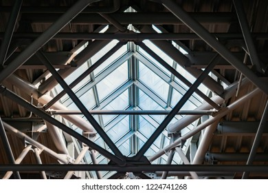 Roof of airport. Metal beams and white ceiling with glass windows. Modern architecture of public place.