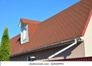 Roof Asphalt Shingles with Moss. Rain Gutter Pipeline with Downspout Pipe and Attic Mansard Window. Roofing Construction, Roofing Repair.