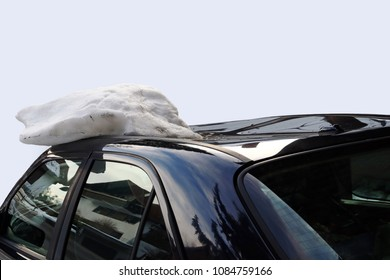 A roof avalanche damaged a black car on the roof. Avalanche of roof damage to a car
