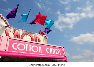 The roof of a carnival cotton candy sale stand has colorful flags on it in front of a blue sky.