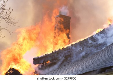 The roof and chimney of a house on fire