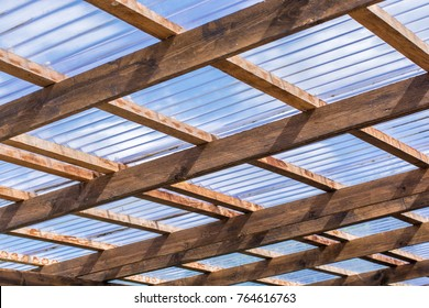 Roof construction of a self-made carport made of wooden beams and transparent roof panels