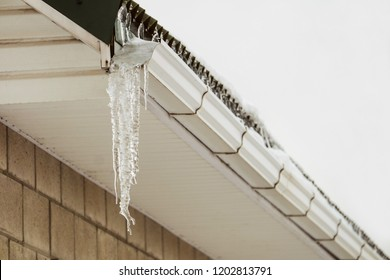 Roof cornice with overhang icy icicle gutter after thaw