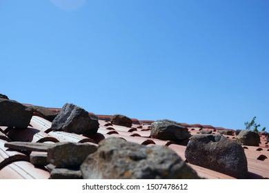 Roof of a country house, covered with red tiles under clear blue sky.  Large stones were placed on the roof to prevent the tiles from flying in bad weather. Close-up with copy space.