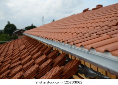 roof cover on housetop with zinc gutter in front: finished roof with red roof tiles cladding on the right side and roofing construction site with uncovered roof tiles on the left side