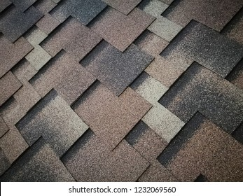 Roof covered by hexagonal soft shingles / tiles in various colors. Abstract geometric background on the subject of modern architecture or construction industry.