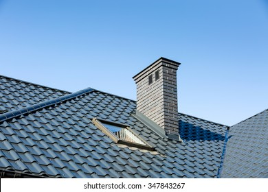 Roof of a detached house with a skylight and chimney against the sky