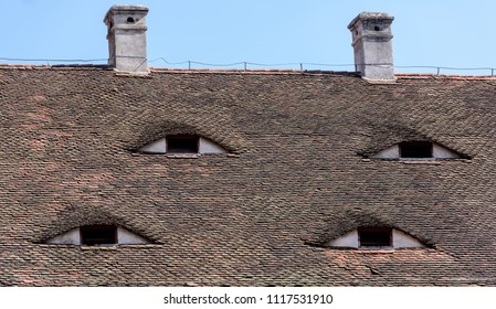 Roof with eye-like windows. Old windows at the top of the house with horns.