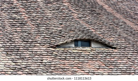 Roof with eye-like windows. Old windows at the top of the house.