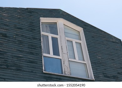 Roof facade of traditional wooden house old painted with horizontal cladding and multi pane window