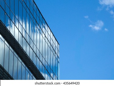 Roof of a glass skyscraper against the sky. Reflection of clouds in windows