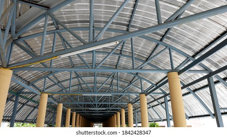 Roof hallway structures. Metal shingle steel frame with cream colored columns in view inside the long corridors of the building. Selective focus