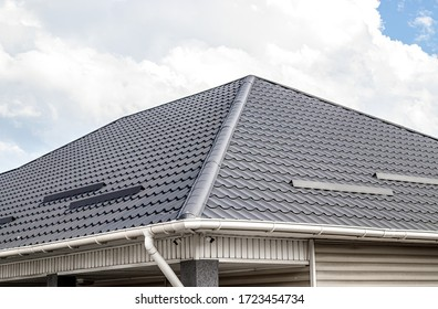 The roof of a house made of metal profile against a blue sky with white clouds