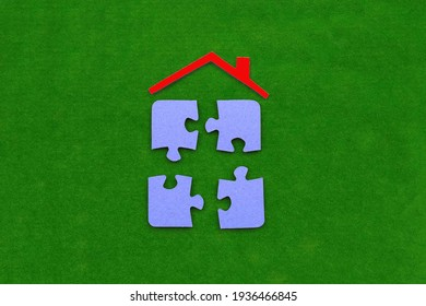 The roof of the house is red, four puzzles are blue on a green background. The concept of shared ownership, the real estate market.