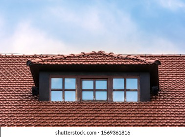 The roof of the house is tiled. Window on the roof of the house. Attic. Blue cloudy sky.