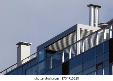Roof of an industrial or office building with ventilation pipes. Tilt photo of abstract modern architecture fragment.