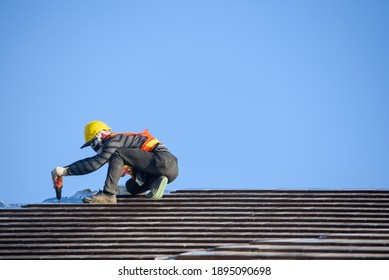 Roof installer Are installing the roof of the house that is Ceramic tile roof at construction site