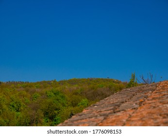 The roof of the lookout tower Erbenova vyhlidka on top of forest hill under the clear blue sky. View over the top of a stone wall