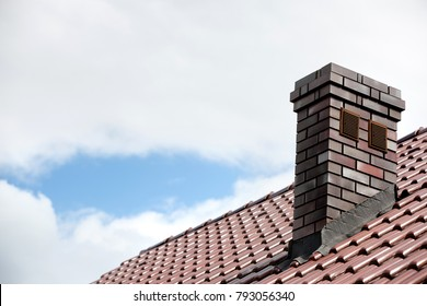 Roof made of ceramic tiles and a brick chimney.
