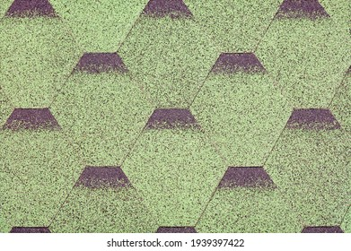 The roof is made of diamond-shaped green bitumen plates overlapping each other. Background and texture of small crumbs, close-up.