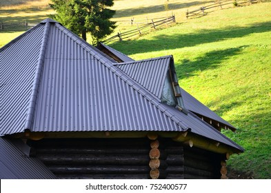 The roof is made of gray embossed metal sheets. Wooden house in the summer field
