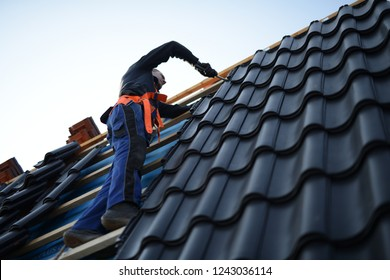 """roof maintenance """"Dach decken"""": worker with roofer tools wearing protective gear on the roof"""