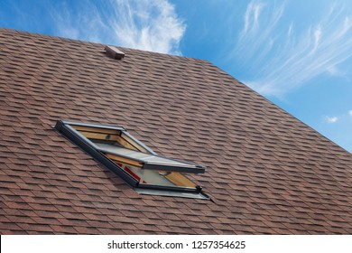 Roof with mansard windows and asphalt shingles.Open skylight on a roof shingles under construction