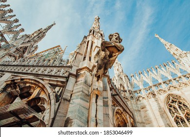 Roof of Milan Cathedral Duomo di Milano with Gothic spires and white marble statues. Top tourist attraction on piazza in Milan, Lombardia, Italy. Wide angle view of old Gothic architecture and art
