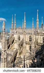The roof of Milan Cathedral (Duomo di Milano) in Milan, Italy. Milan Cathedral is the largest church in Italy and the main travel attraction of Milan. Duomo on the blue sky background.