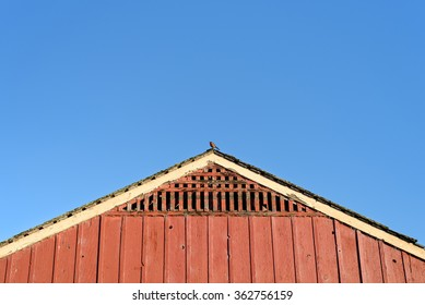 Roof of an old red barn with a bird sitting on its peak.