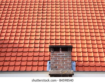 Roof with red clay tiles and a brick chimney.