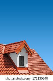 roof with red tiles on a background of blue sky, new roof