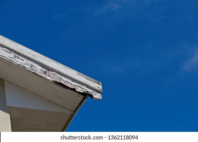 Roof repair and maintenance concept image consisting of old rotting fascia boards and a blue sky background.