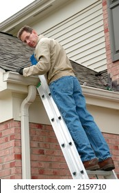 Roof Repair - Man on a ladder, cleaning the gutters and repairing the roof shingles.