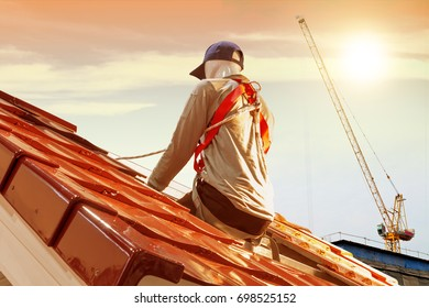 Roof repair, men model worker replacing tiles on the roof with sunlight background