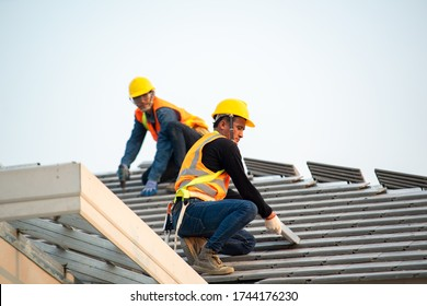 Roof repair,Construction worker using nail gun to install new roof on top roof,Residential building under construction concept