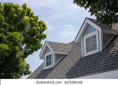 Roof shingles with garret house on top of the house among a lot of trees. dark asphalt tiles on the roof background - Shutterstock ID 1672585168