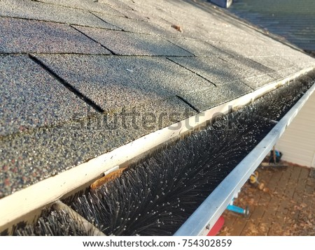 roof shingles and gutter with black gutter guard pipe cleaner