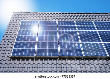 Roof with solar panels fragment under sunny blue sky
