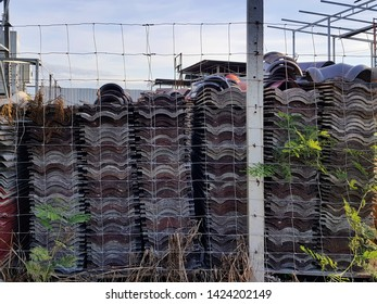 Roof Tile Stacks by the Fence at Warehouse Construction Site