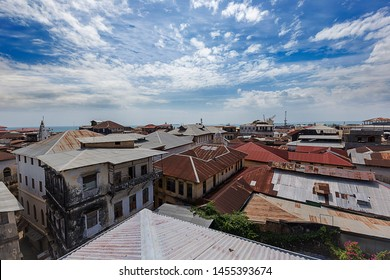 roof top aerial view above zanzibar town buildings looking at cubist roof sheeting and the distant ocean along the horizon