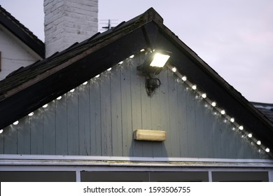 Roof top of the house with installed illumination. The large flood light and small decorative lights.