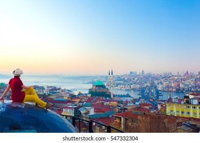 Roof Top View of Istanbul City and Gulf female Traveler sitting and overlooking bright Sunrise