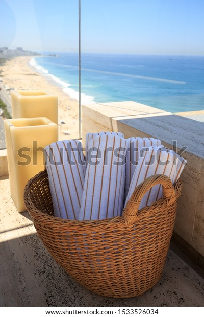 Roof top view through a picture window of Copacabana Beach, Brazil  with a wicker basket with clean white and brown stripped towels with large candles in the background.