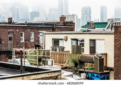 Roof tops of the old part of Kensington Market set against modern skyscrapers.