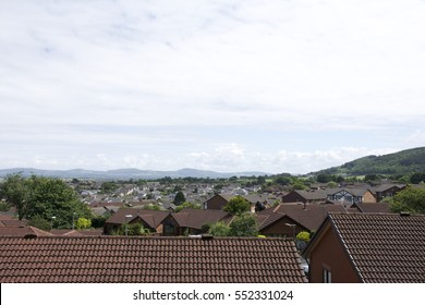 Roof tops of village in Britain with surrounding countryside, mountains, hills and blue sky and clouds 2 of 2