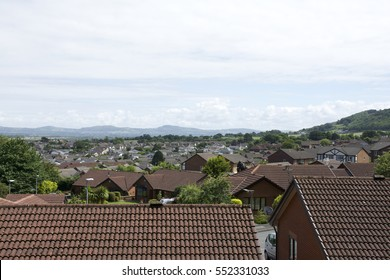 Roof tops of village in Britain with surrounding countryside, mountains, hills and blue sky and clouds 1 of 2