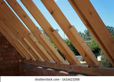 Roof trusses not covered with ceramic tile on a detached house under construction, visible roof elements, battens, counter battens, rafters. Industrial roof system with wooden timber, beam